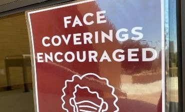 """-""""Face Coverings Encouraged"""" signs have recently been posted around campus."""