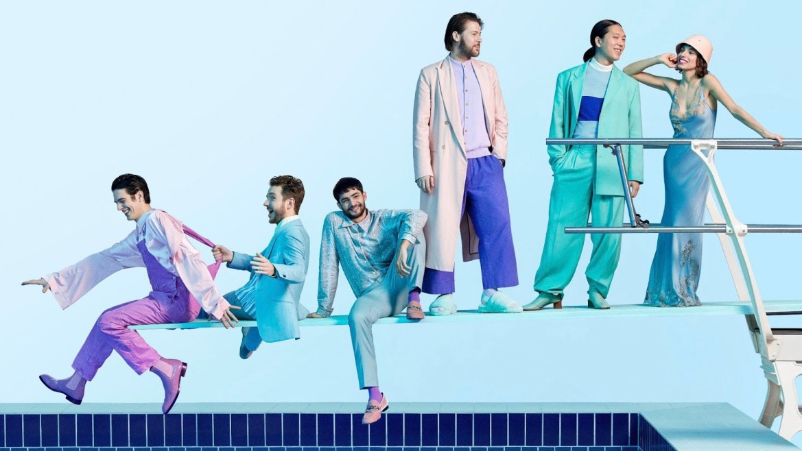 A picture of six people posing on a diving board, dresses in pastel blues and purples.