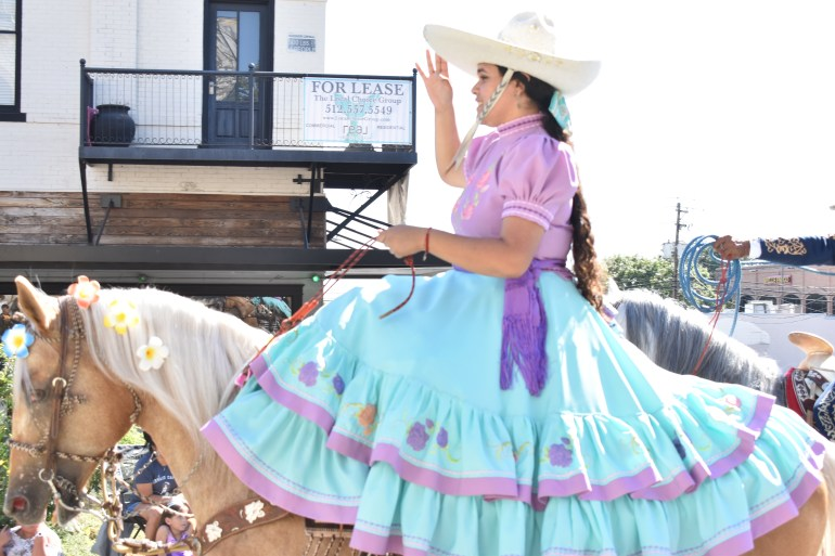 A woman riding a horse smiles at parade-goers from atop a horse, She has a beautiful blue skirt that is displayed, and the horse has flowers in its' mane.