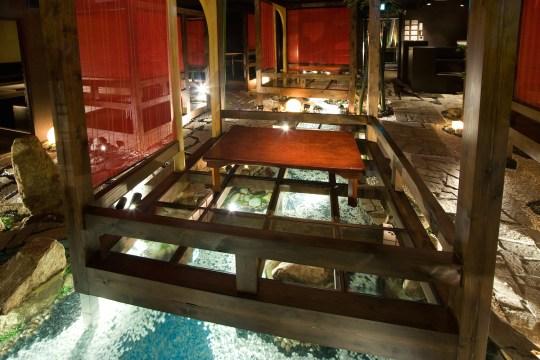 川にまたがる個室の床はガラス張りとなっており、床下のせせらぎを見る幻想的な体験を提供します。