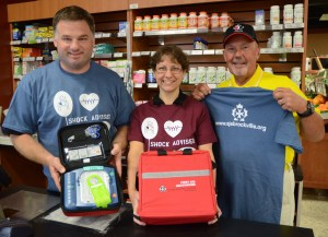 Neil Kudrinko and staff member, Monique Byrne, accept a Public Access Defibrillator from David Dargie of St. John Ambulance Brigade of Leeds-Grenville and Lanark. Kudrinko's in Westport is now one of the few retail spaces to have a defibrillator installed.