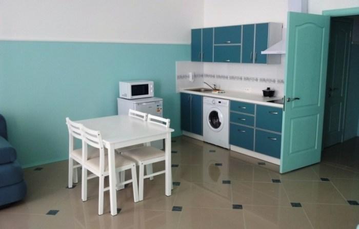 Стиральная машина на кухне, стоящая между шкафами