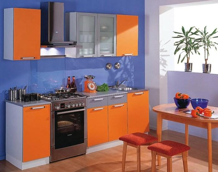 Оранжевые шкафчики на кухне на фоне синей стены