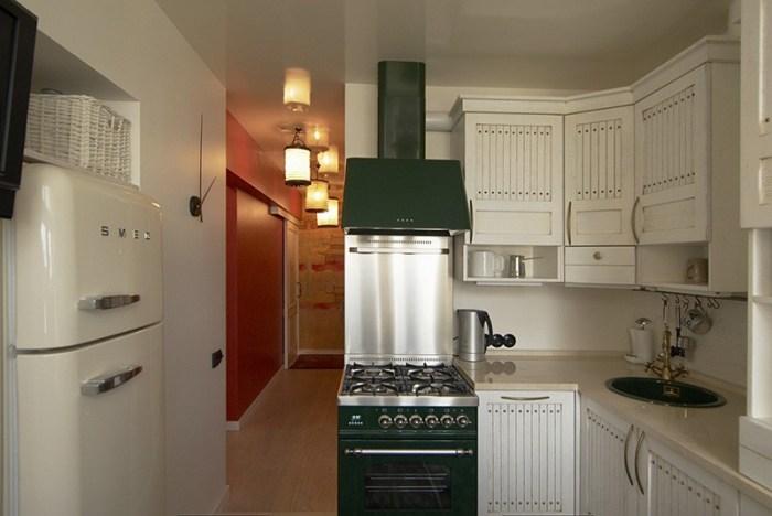 Холодильник в стене между маленькой кухней и комнатой