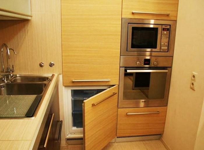 Маленький холодильник в высоком шкафу на кухне