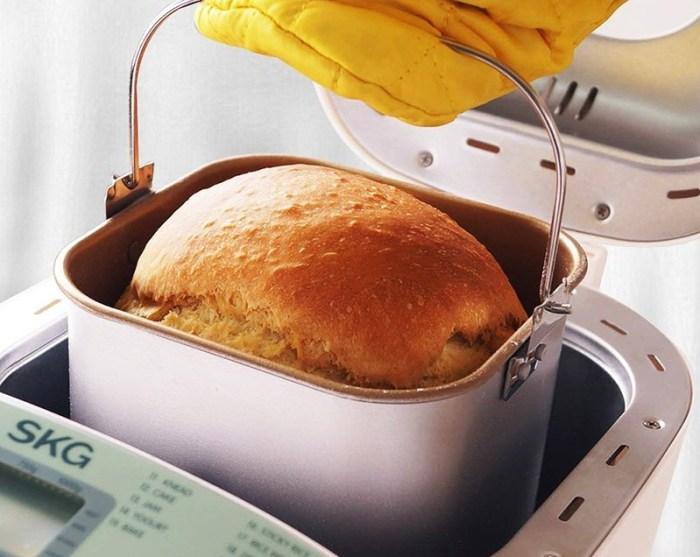 Из хдебопечки вынимают ведро с горячим хлебом