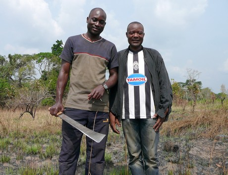 Community members Serge Etele, at left, and Viany Abia at the community's farm in Cameroon. (Photo by Nama Naser)