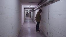 Rundgang im Keller der Polizeizentrale. Der Mann, der den Kopf an die Wand lehnt ist ein Geomant, der versucht die Energie des Hauses zu fühlen