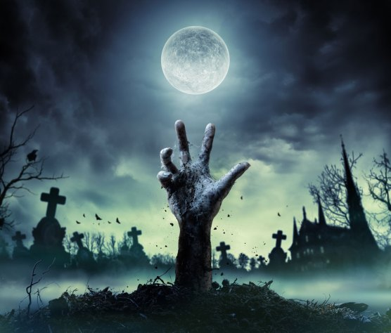 Zombie Hand Rising Out Of A Graveyard In Spooky Night c) shutterstock