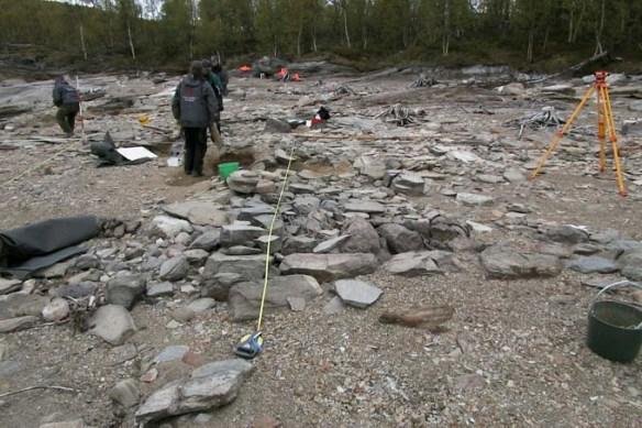 Måttband och avvägningsinstrument i Silbojokk år 2004. Det är inte en teodolit och definitivt inte en trilobit! Avsaknaden av vegetation beror på att sjön Sädvajaure årligen däms upp av en kraftverksdamm. ©Norrbottens museum. Foto Åsa Lindgren