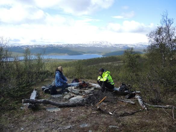 Lunch vid Tjiktjac-stugan, med utsikt över sjön Vuoggatjlme och snöklädda fjäll.
