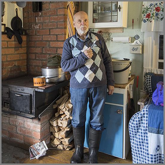 En man står i ett kök med järnspis