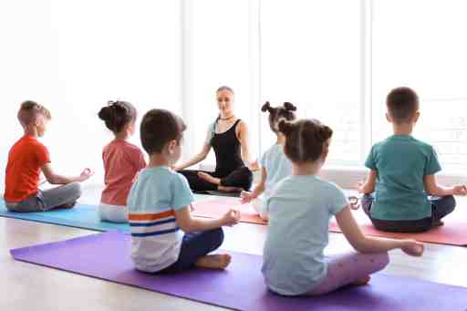 students sitting on mats facing yoga teacher, sitting in easy seated yoga pose with hands in a mindfulness mudra on knees