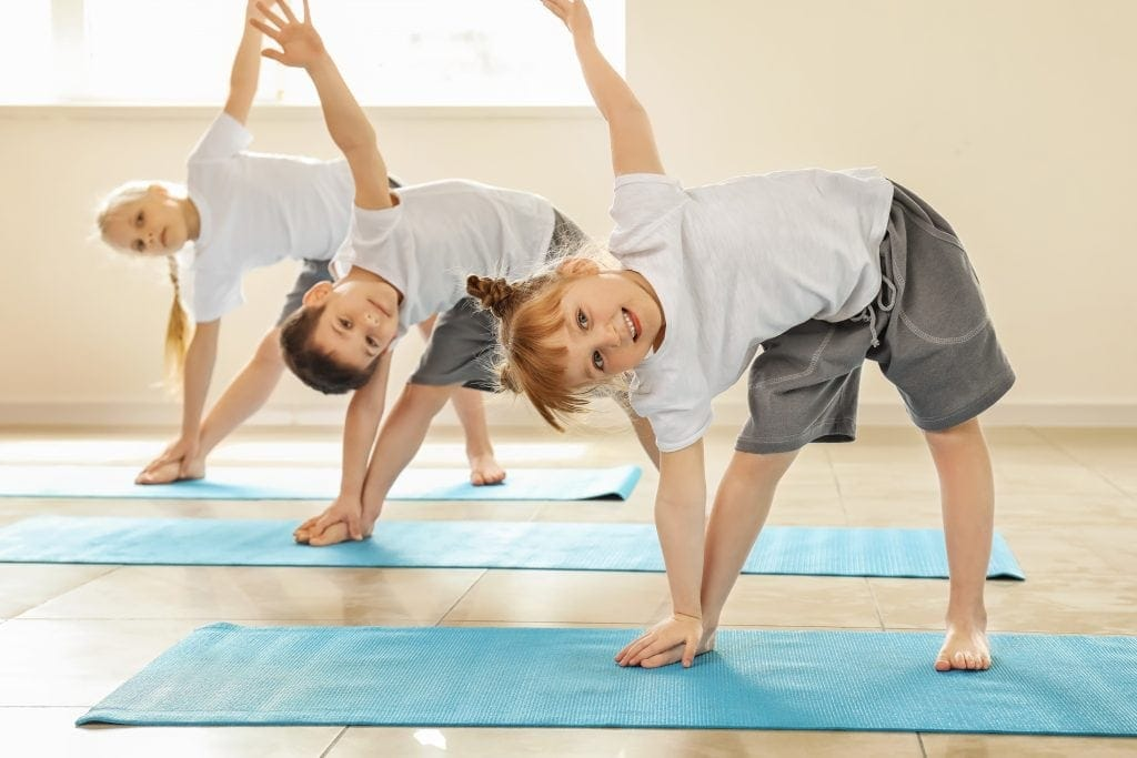 three kids showing triangle pose for a shapes yoga math class
