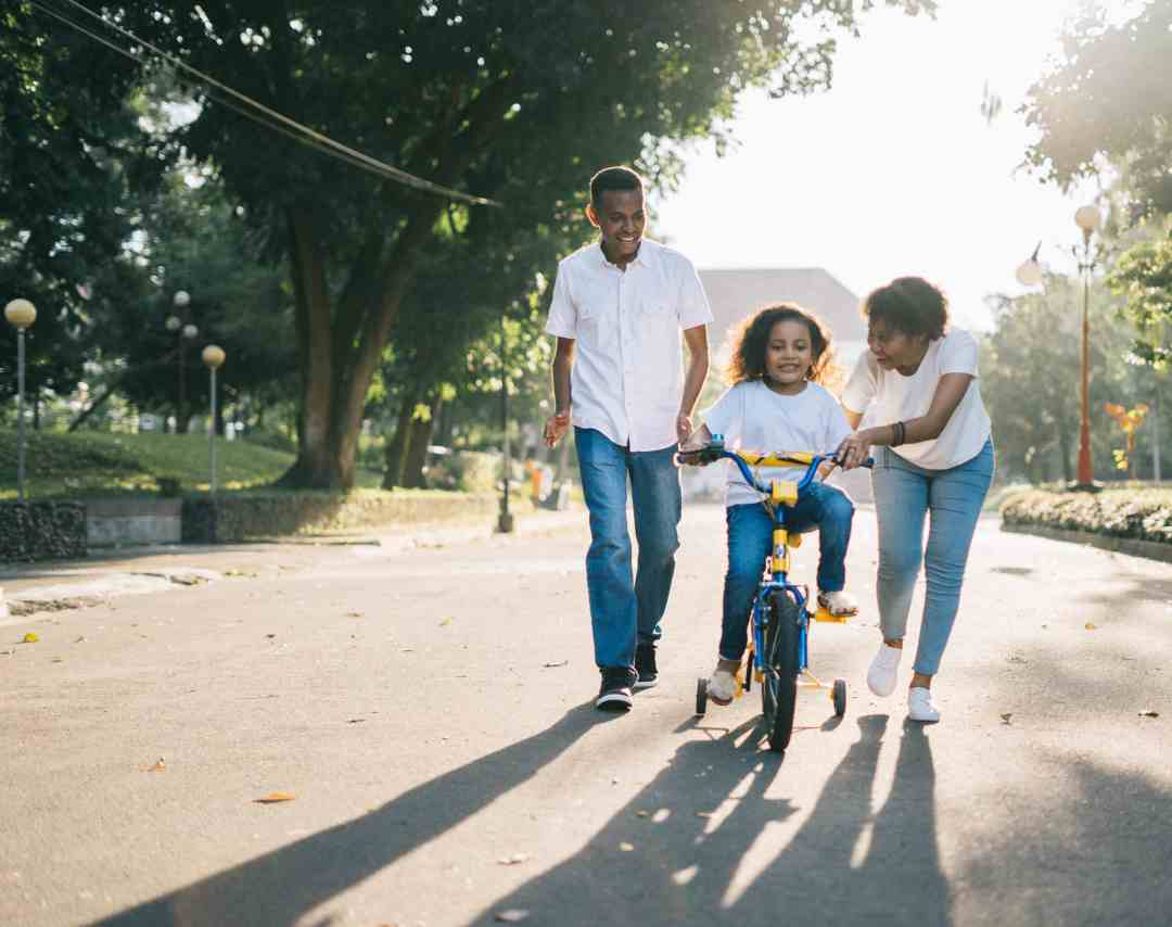 family with kid learning to ride a bike teaching a growth mindset