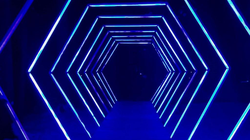 Zu sehen sind mehrere Neonröhren, die in der Form zahlreicher Sechsecke angeordnet ist.