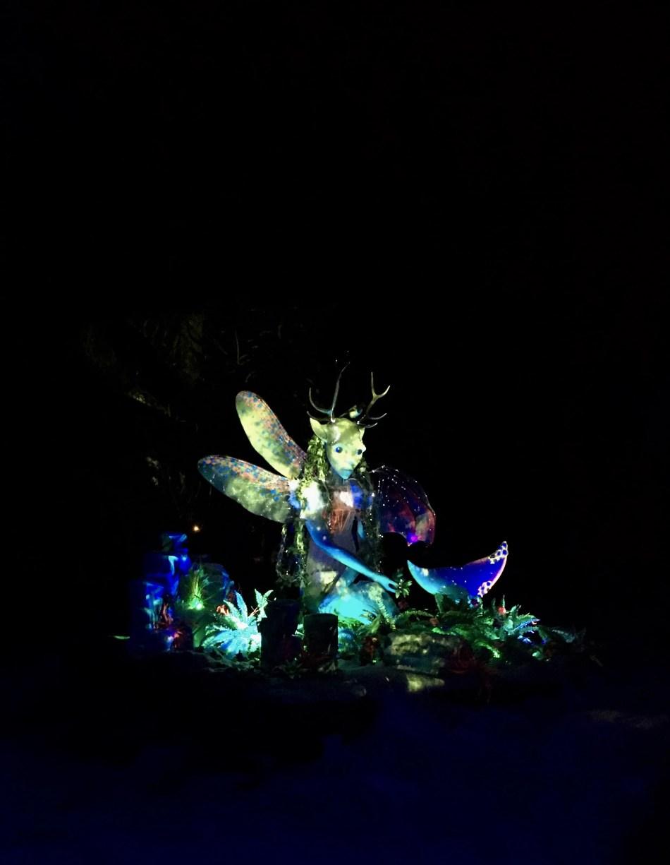 Zu sehen ist eine Skulptur, die bunt beleuchtet ist. Sie hockt zwischen beleuchteten Pflanzen.