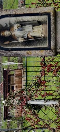 Eine Heiligenskulptur in einem steinernen Tabernakel im Vordergrund. Dahinter Weinberge.