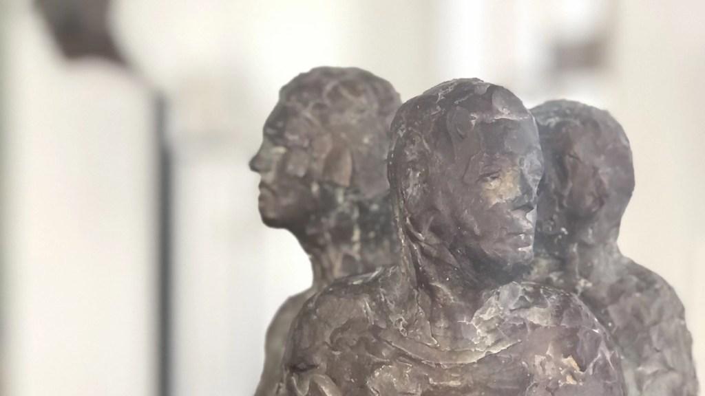 In Bronze gegossen sind drei Köpfe zu erkennen.