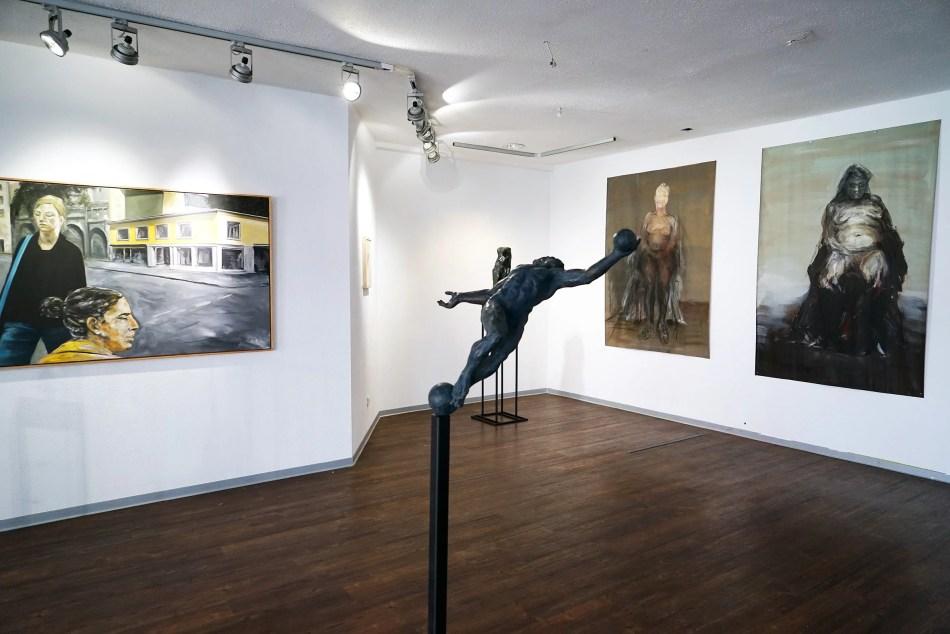 In Bildvordergund ist auf einem dünnen Eisenstab eine Plastik auf Bronze zu erkennen – in Rückenlage, kurz vor dem Fallen. Link im Bildraum ein Gemälde, Rechts im Bildraum zweich große Arbeiten, auf denen weibliche Akte zu erkennen sind.