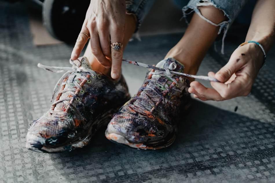 Felisa Rauschenberger schnürt ihre Arbeitsschuhe, die voll mit Farbe bedeckt sind.