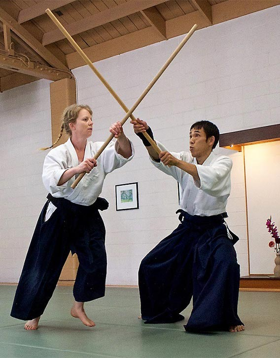 Aikidokas practicing with the Jo staff