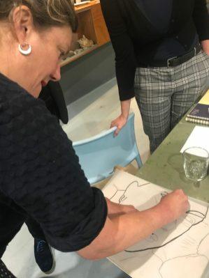 Rosemin laat zien hoe je de lijnen van je gezicht met houtskool natrekt om ze later op je tekenpapier te kunnen uitwrijven.