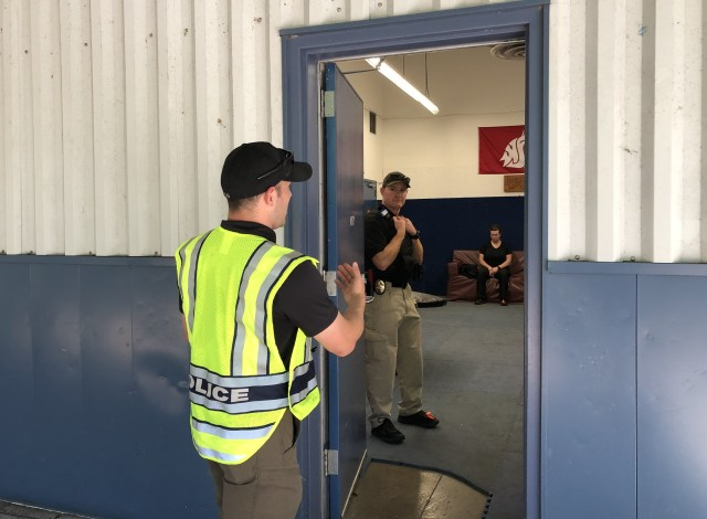 caption: Tukwila police officer Dustin Johnson, left, reviews a training scenario at the state's training academy in Burien.