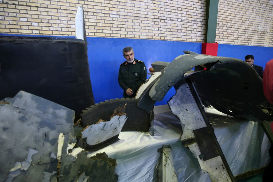 Head of the Revolutionary Guard's aerospace division Gen. Amir Ali Hajizadeh looks at debris from what the division describes as the U.S. drone which was shot down on Thursday, in Tehran, Iran, Friday, June 21, 2019. Major airlines from around the…