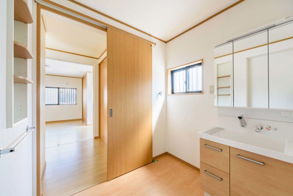 温かみのある落ち着く洗面空間。棚やタオル掛けも設置して利便性もアップ。