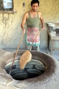 Gospodarz dwoma kijkami zręcznie wydostawał z zionącego gorącem pieca świeżutkie puri Fot. Waldemar Szełkowski