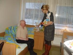 Doradcamer Elżbieta Jabłońska wręcza świąteczne prezenty pensjonariuszom ośrodka