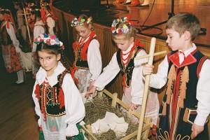 """Opłatek  przywieźli na drewnianych wózeczkach wysłanych siankiem mali uczestnicy """"Wilenki"""" Fot. Jerzy Karpowicz"""