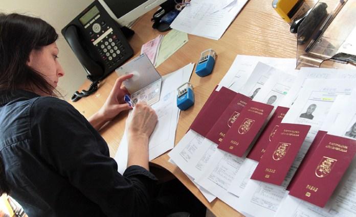 Kobieta pracująca przy stosie litewskich paszportów