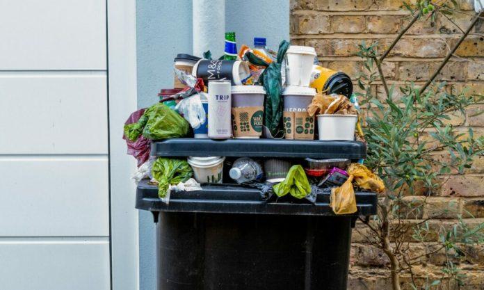 Przepełniony czarny pojemnik na śmieci z wieloma wysypującymi się odpadami