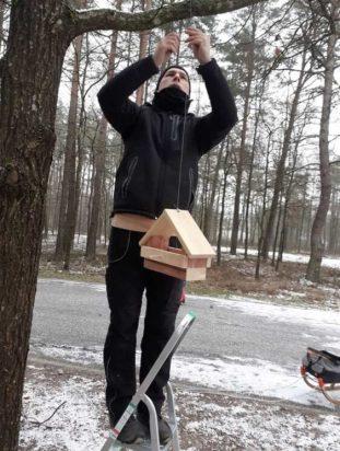 Andrej Smirnow zawiesza własnoręcznie wykonany karmnik dla ptaków na drzewie w parku w Mariampolu