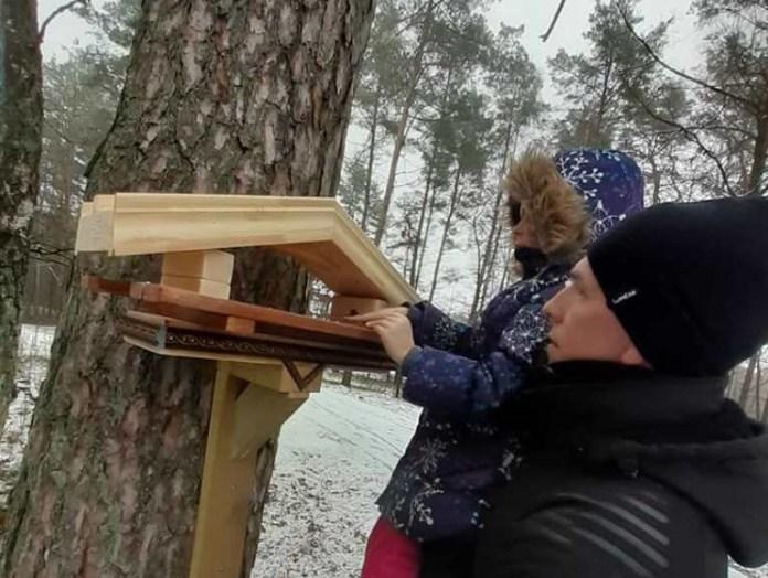 Andrej Smirnow z Mariampola zawiesza własnoręcznie wykonany drewniany karmnik dla ptakówm