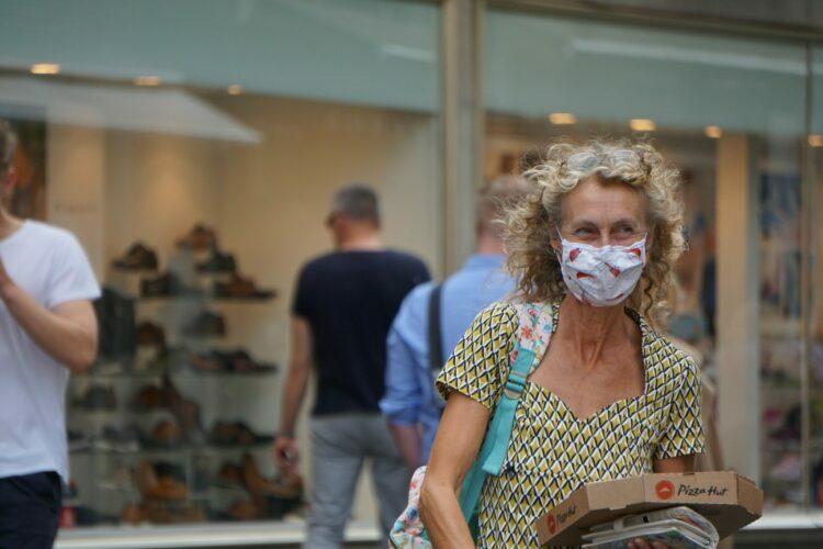 Kobieta o kręconych blond włosach z maską ochronną zasłaniającą nos i usta