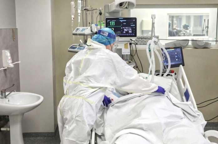 Medyk opiekuje się chorym pacjentem w szpitalu na Litwie.