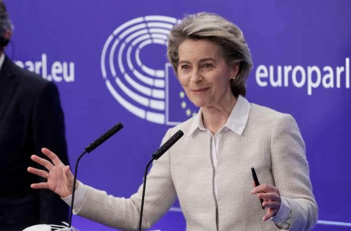 Ursula von der Leyen stoi i uśmiecha się wymachując rękoma.