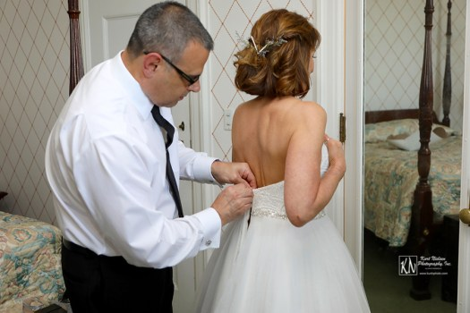 zipping up the wedding dress
