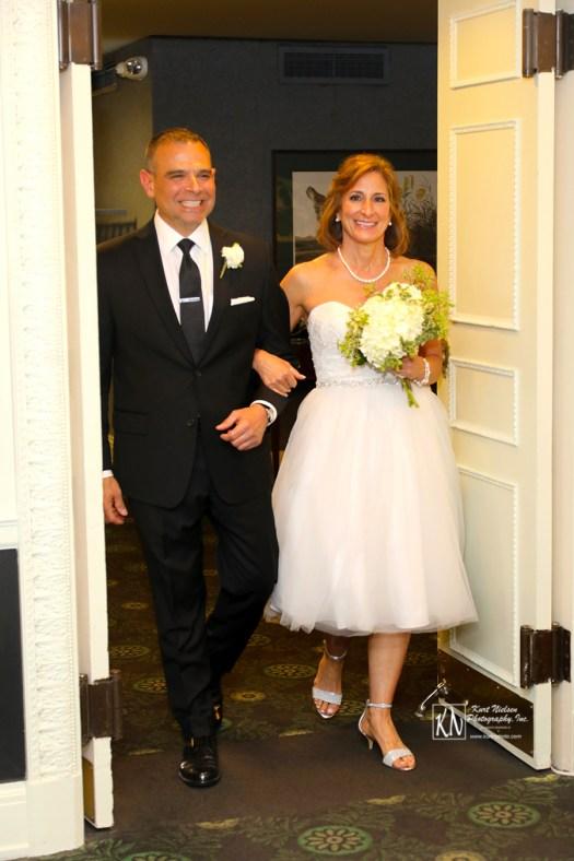 groom walking his bride down the aile