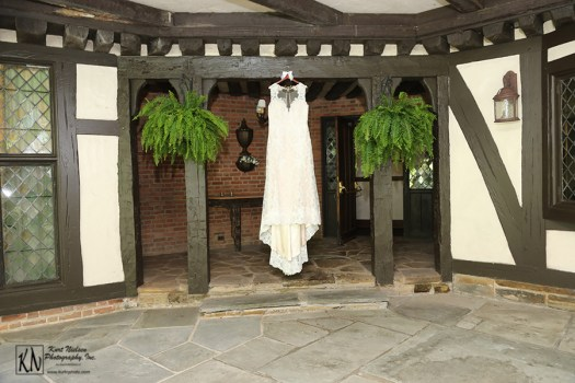 ivory Ashland wedding dress designed by Vatana Watters hanging between two ferns on the covered patio of the Club at Hillbrook
