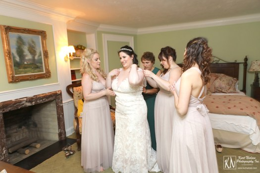 the bridesmaids helping the bride get dressed at the Club at Hillbrook