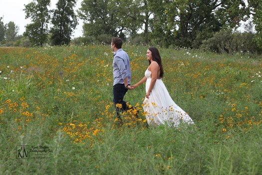 walking in a field of wildflowers for their engagement portraits