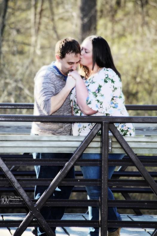 romantic spring engagement photo on a bridge