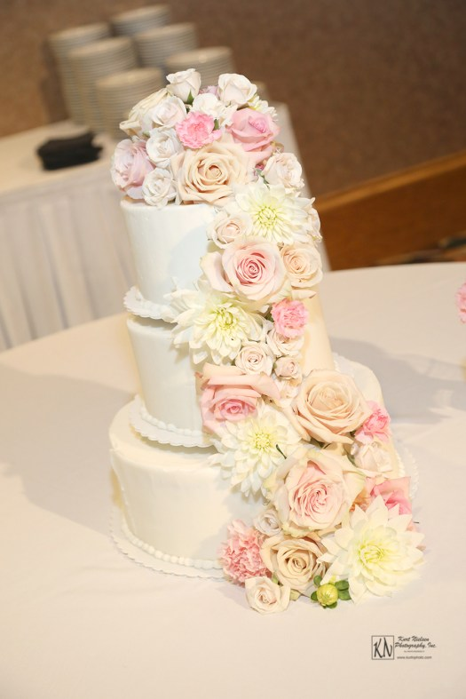 fresh cut blush nude and white flowers cascading down a fondant covered wedding cake at The Pinnacle