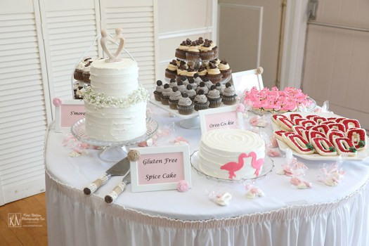 wedding cake table with cookies and cupcakes