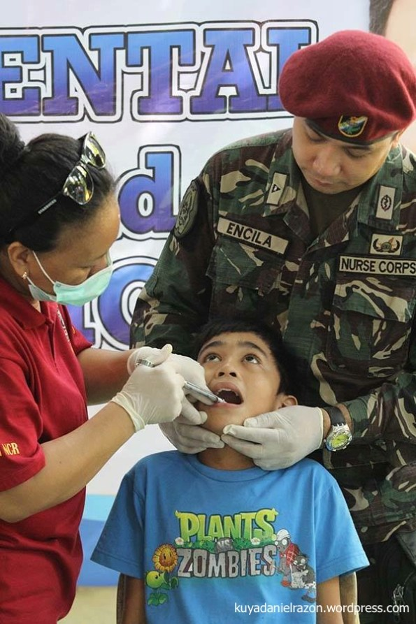 "A boy fearlessly opens his mouth to the dentist administering anaesthetic during the UNTV Action Center ""People's Day"" event last April 25th. Free dental extraction, cleaning and other services were given by volunteer dentists assisted by military medical units cooperating in the said event."