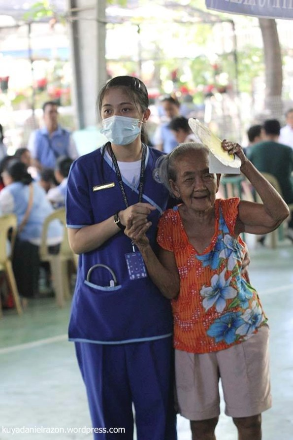 An elderly woman smiles radiantly as she was assisted by one of the volunteer nurses as she finds her way through all the servicing doctors and other public service offerings.